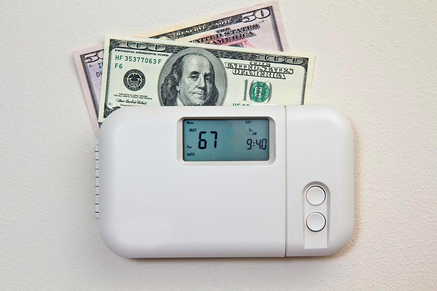 thermostat with cash in it indicating cost of heating