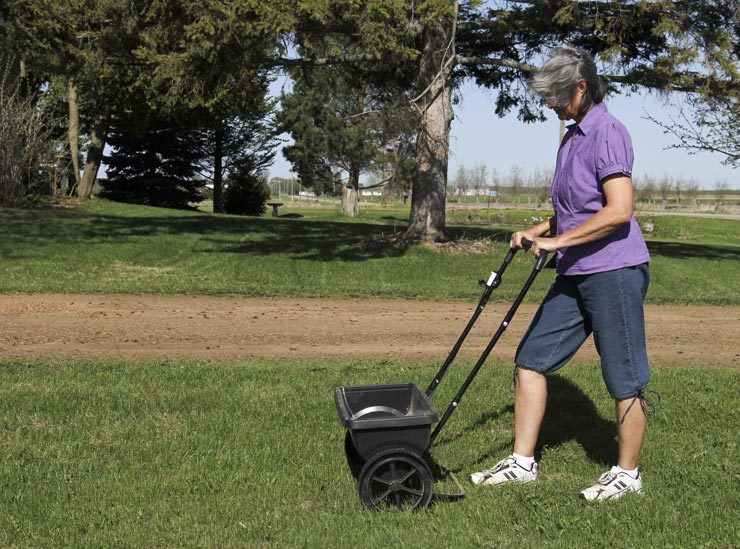 woman using fertilizer spreader