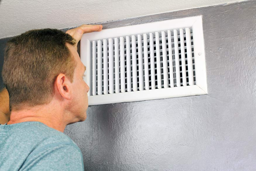man installing a heater vent