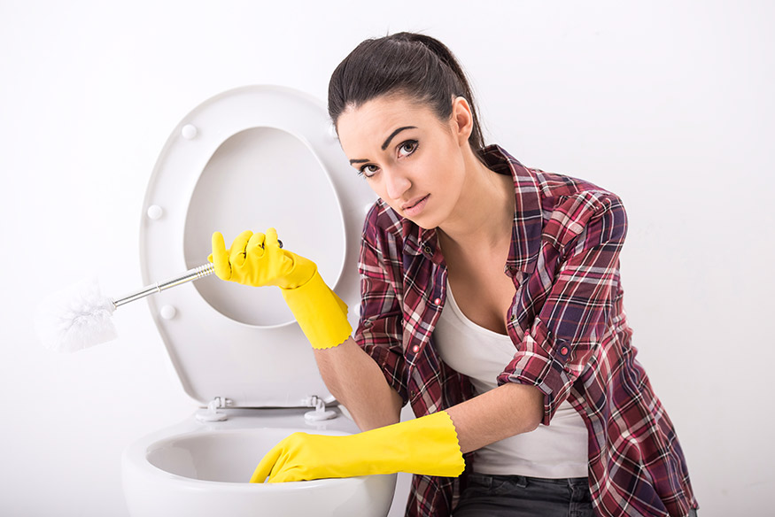 woman cleaning toilet bowl stains