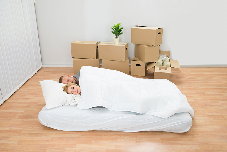 couple sleeping on mattress on the floor after moving house