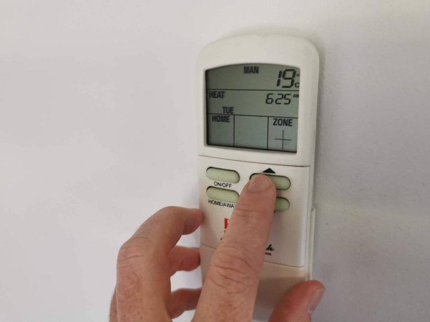 man using digital thermostat