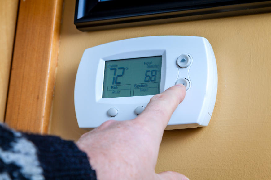 A person lowers temperature on a home digital thermostat
