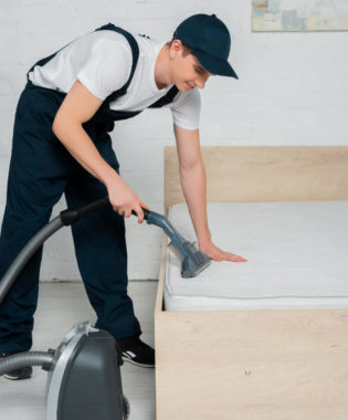 man vacuuming bed to get rid of bugs and eggs