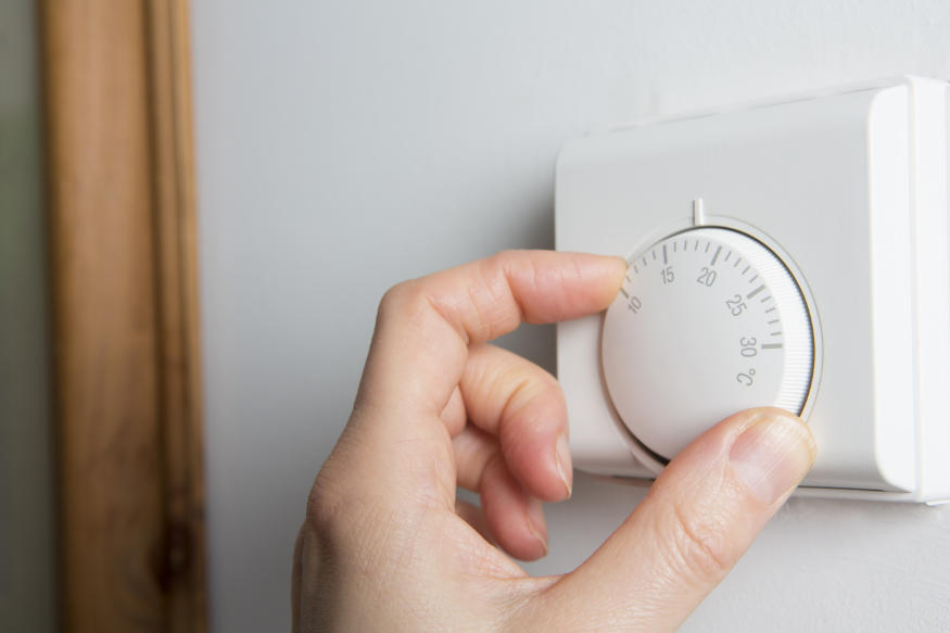 Close Up Of Female Hand On mechanical Heating Thermostat