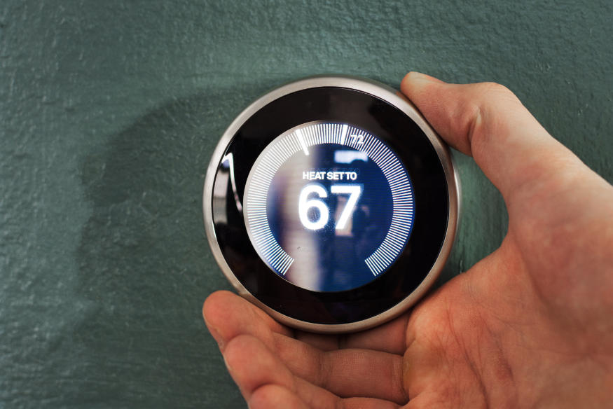 Nest smart home thermostat being adjusted by users hand