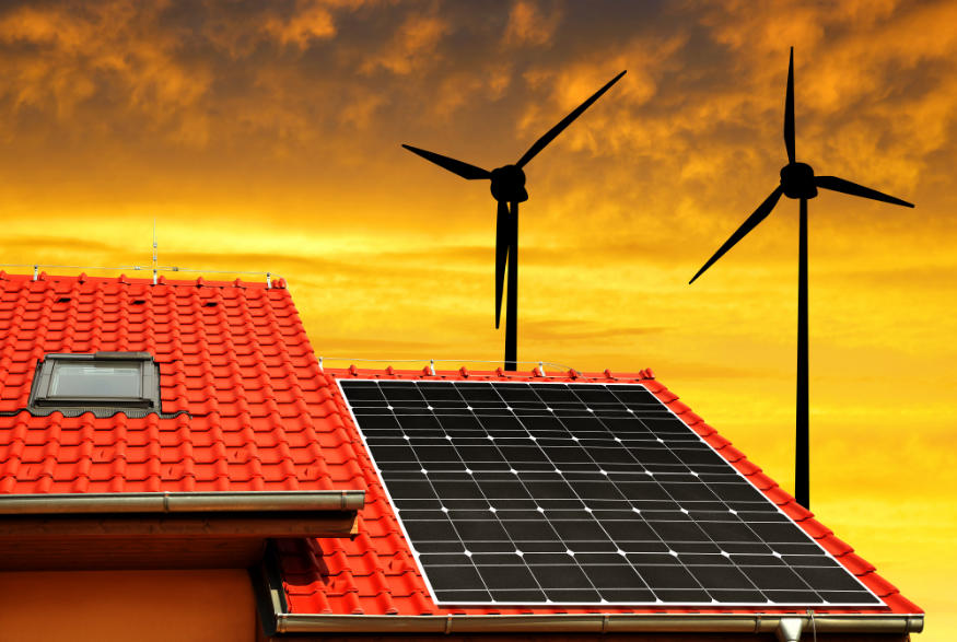 solar power on the roof of a house with wind turbines in the background