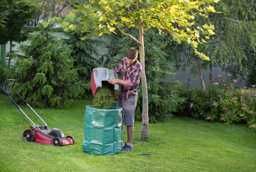 man emptying lawn clippings into compost bag