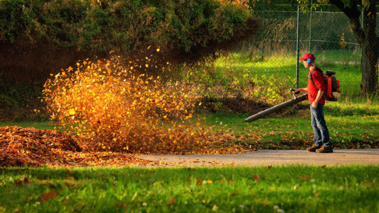 man using a high CFM leaf blower