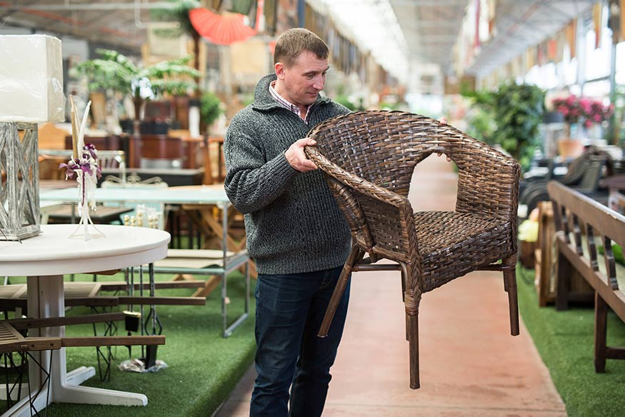 man inspecting wicker chair in furniture store