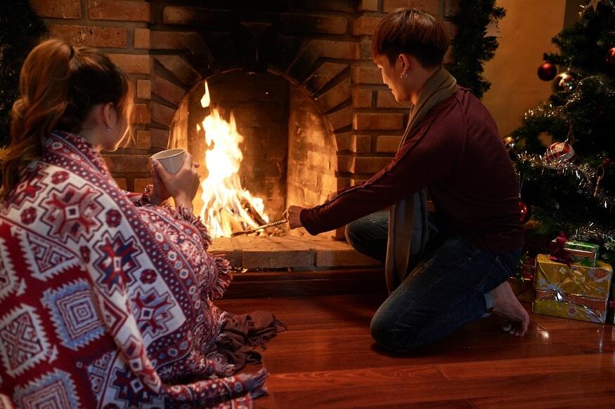 man adding wood to fireplace