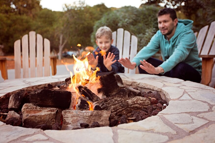 dad and son sitting near a fire pit