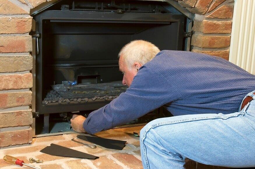 man fixing gas fireplace