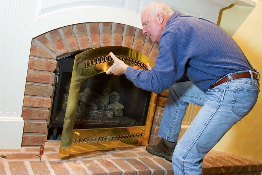 man removing gas fireplace door