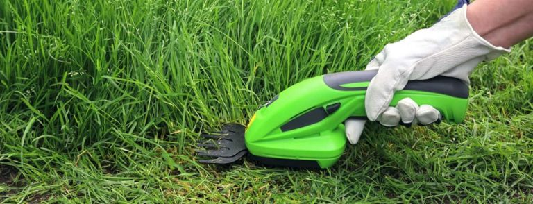 Man using cordless grass shears to trim overgrown grass