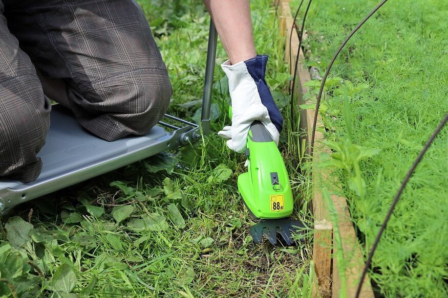 man using cordless grass shears in the yard