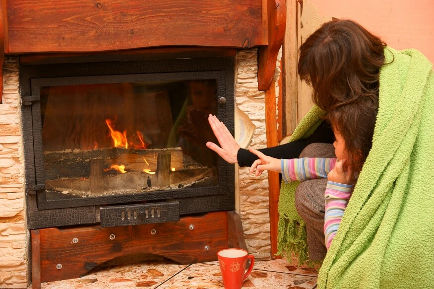 woman and child enjoying heat from fireplace insert