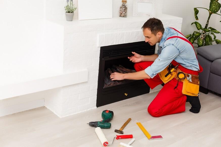 man installing a fireplace insert
