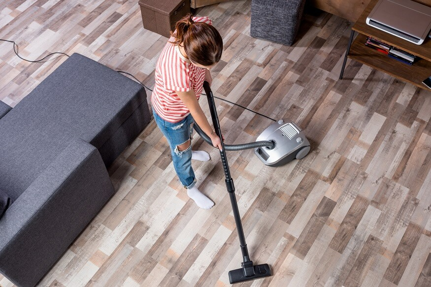 woman using a vacuum to clean the house