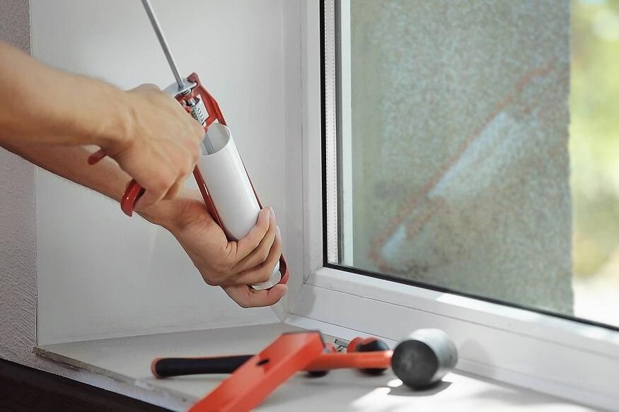 man adding silicone caulk to a window