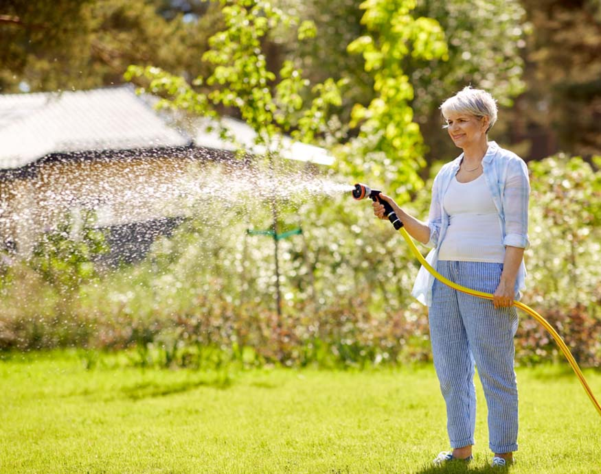 woman use a hose to water the lawn before lawn fertilizer application