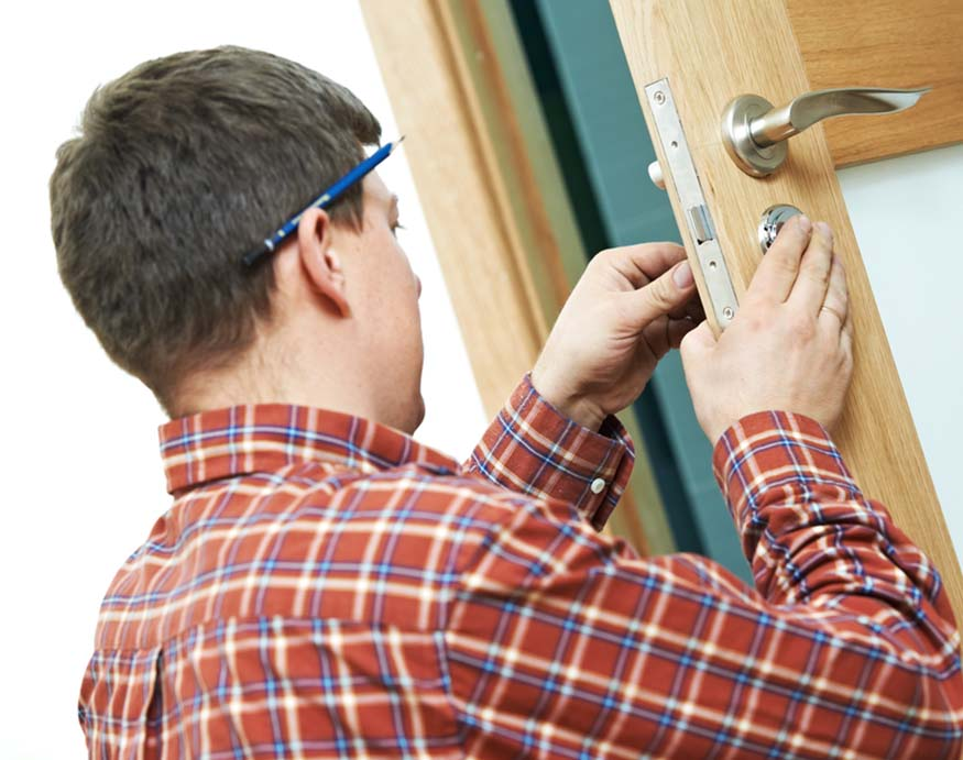 carpenter installing a new door lock