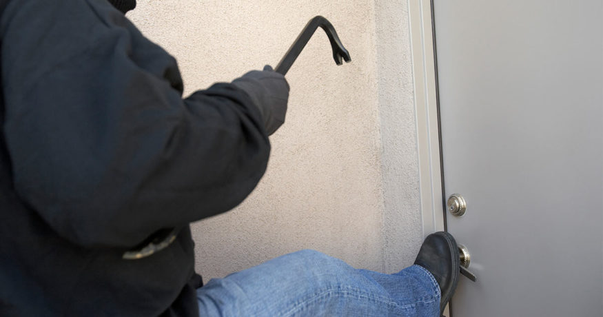 burglar kicking in door to house with a crowbar