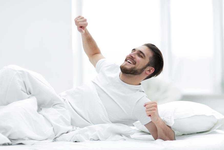 man waking up on bed