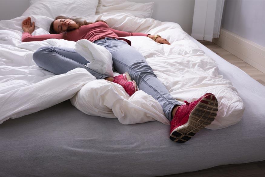 woman sleeping on a mattress on the floor