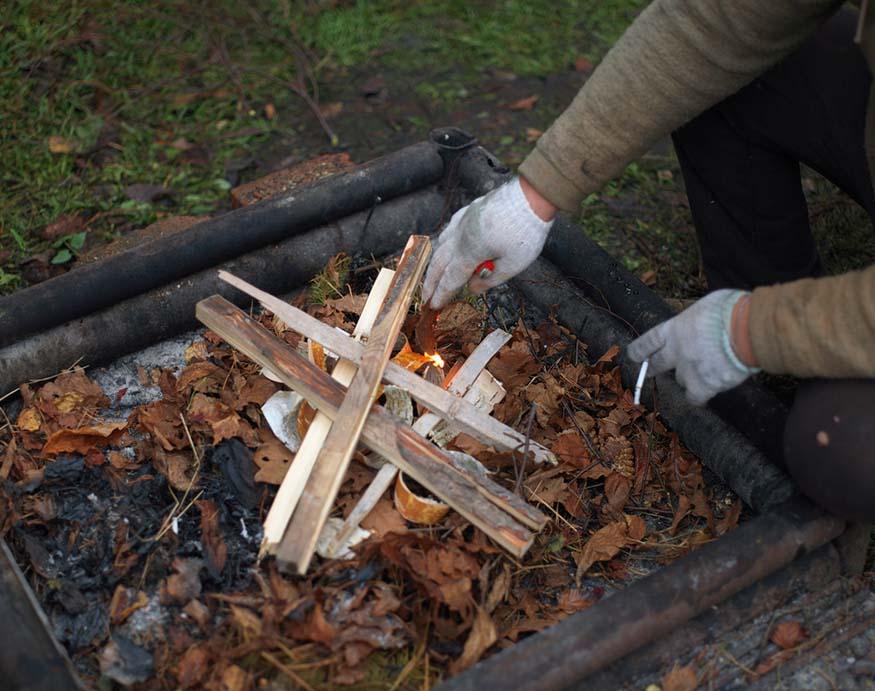 man starting a bonfire outdoors