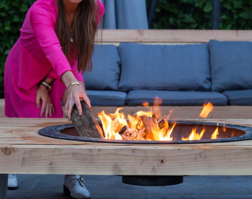 woman adding logs to the fire pit