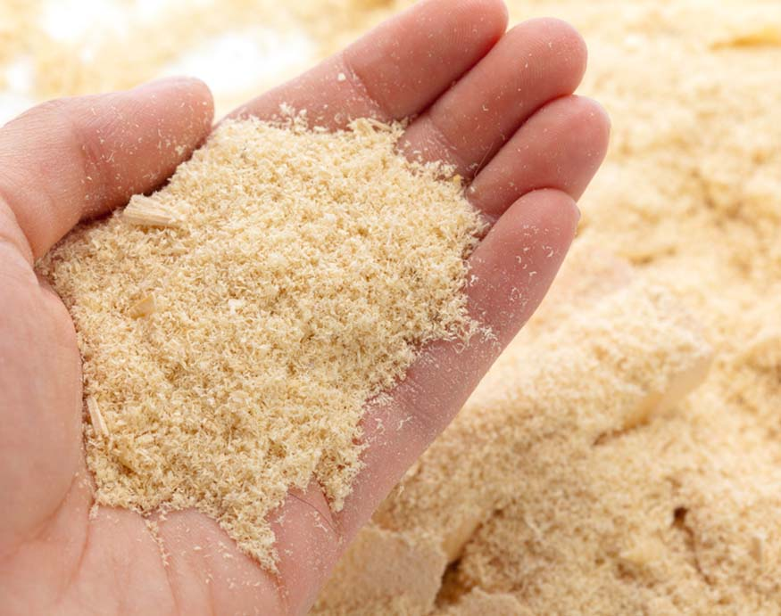man holding a handful of sawdust