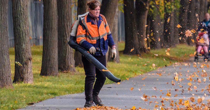 woman using backpack leaf blower