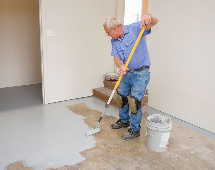 man painting the garage floor