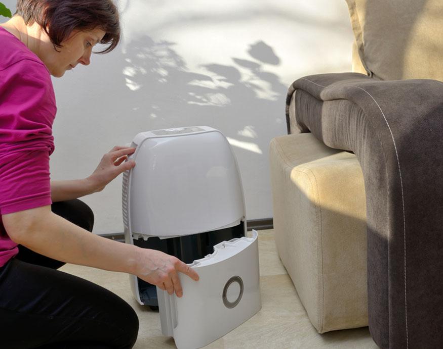 woman setting up a dehumidifier