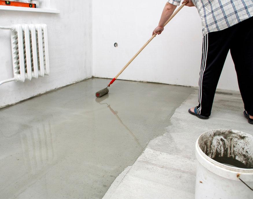 man applying garage floor paint