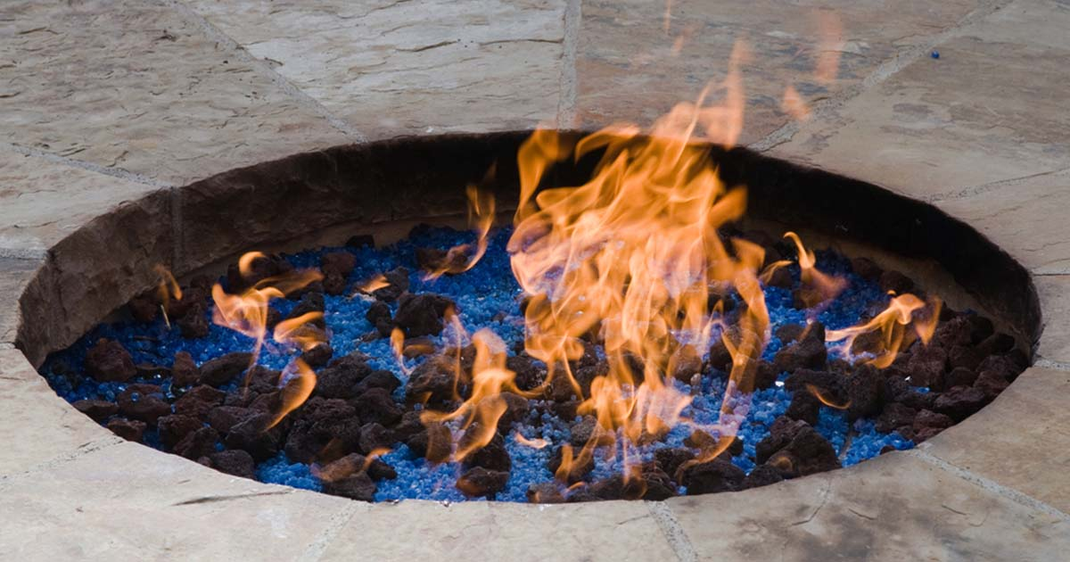 burning fire pit with fire glass and lava rock