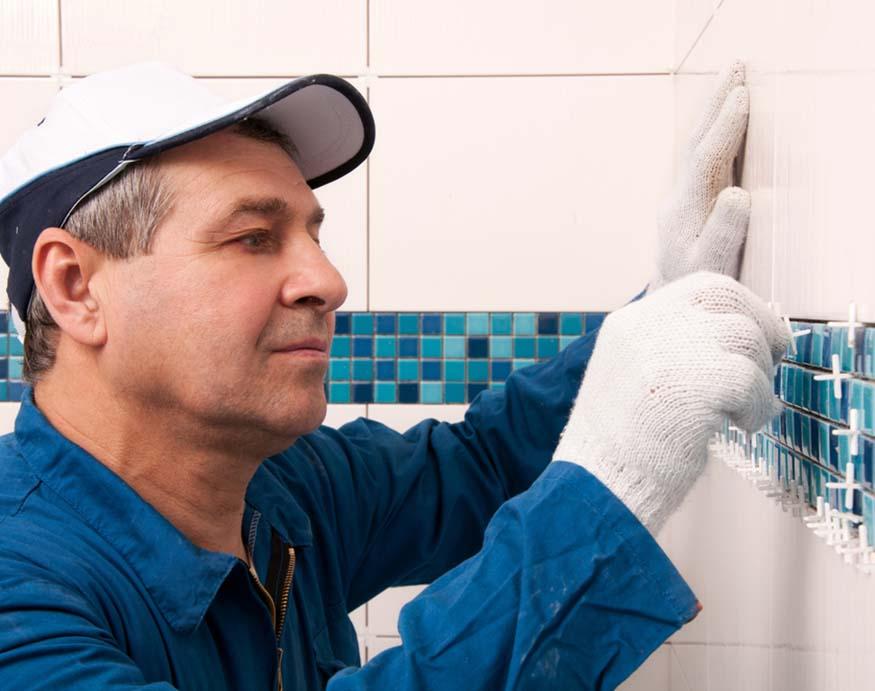 man installing bathroom wall tiles