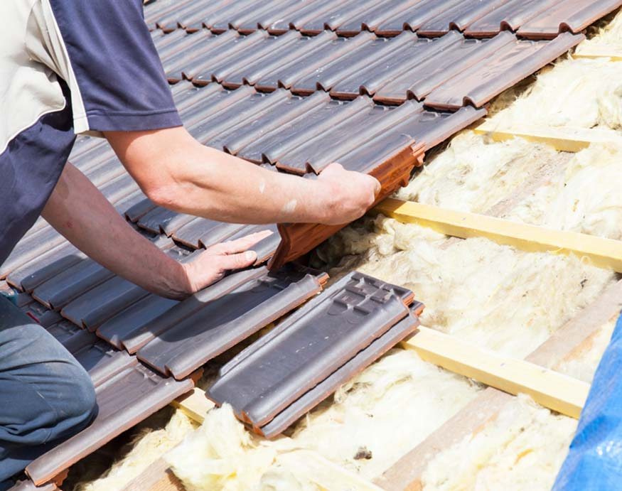 man adding new roof tiles