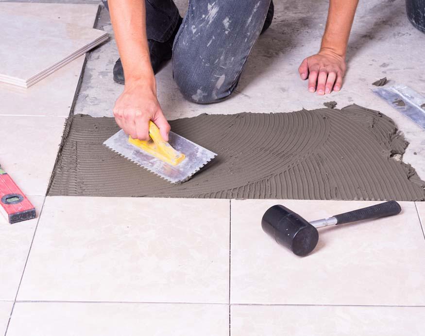 "man putting 4"" tiles"