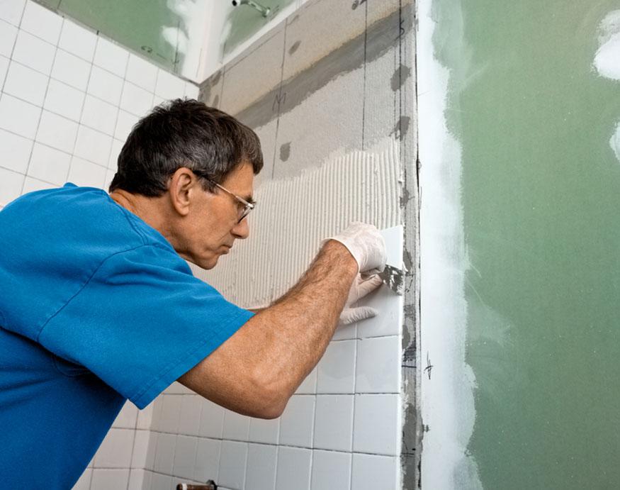 man installing shower wall tiles