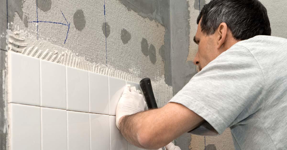 man installing bathroom tiles on wall