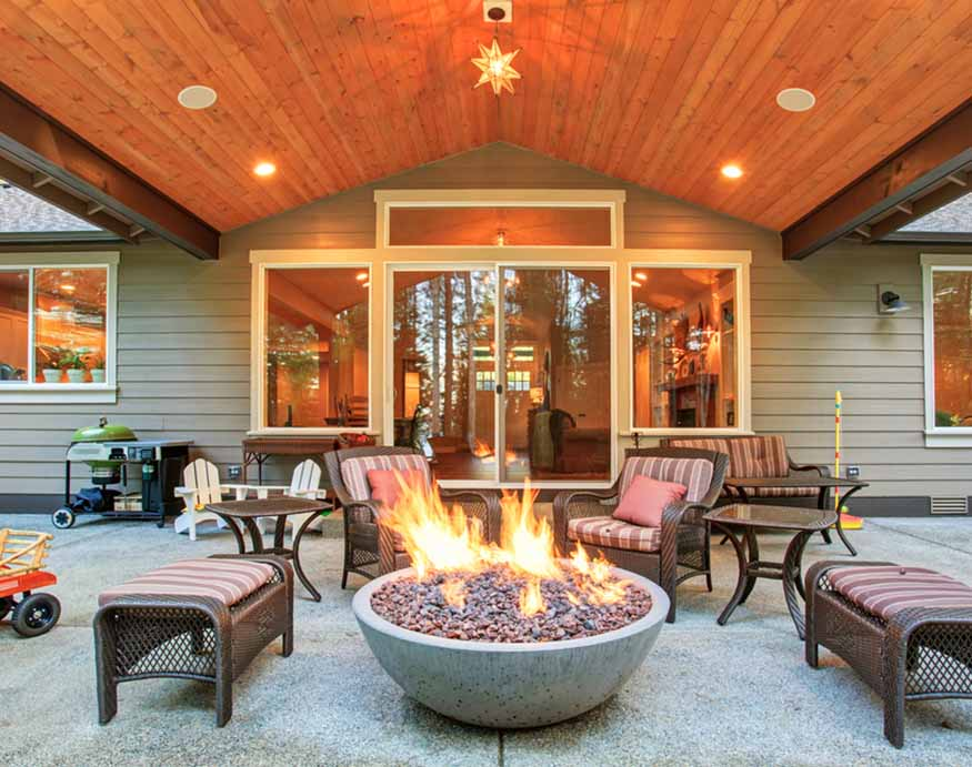 large backyard with burning lava rocks in the fire pit