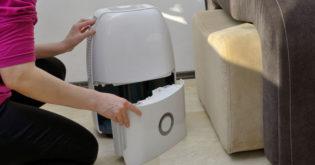 woman fixing a leaking dehumidifier