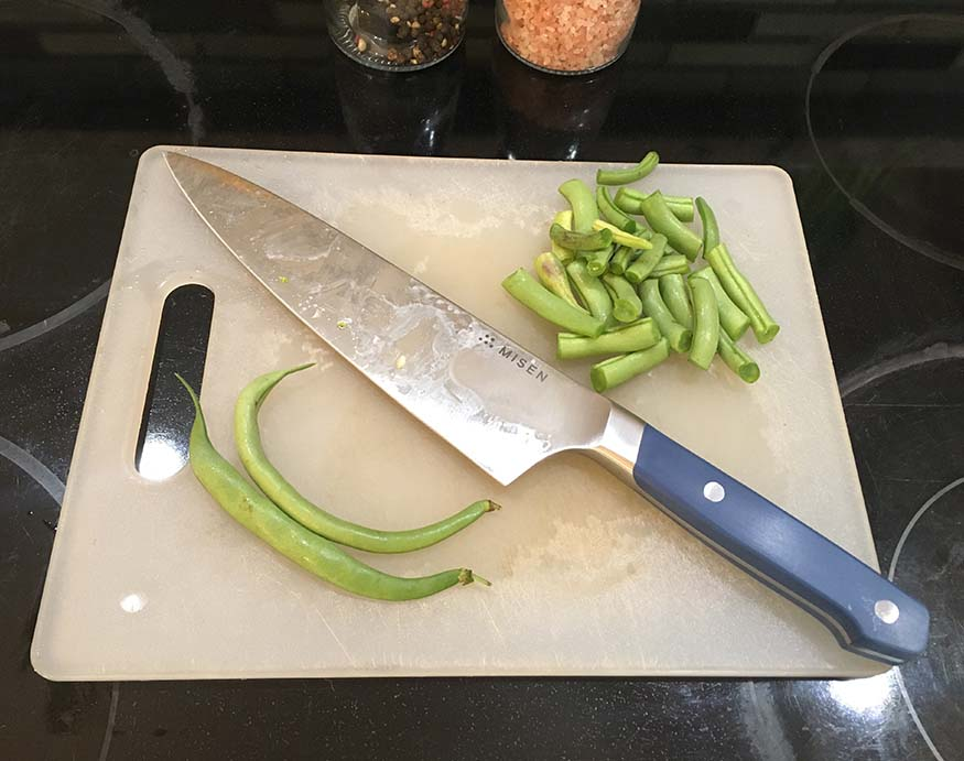 Misen Chef's Knife and green beans on a plastic cutting board