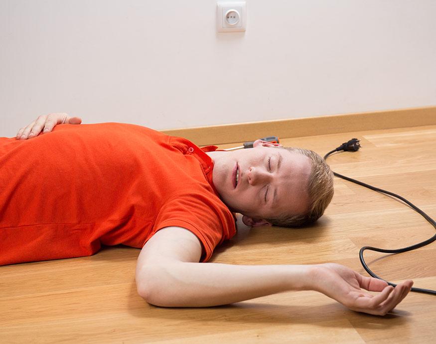 An electrician lying on the floor