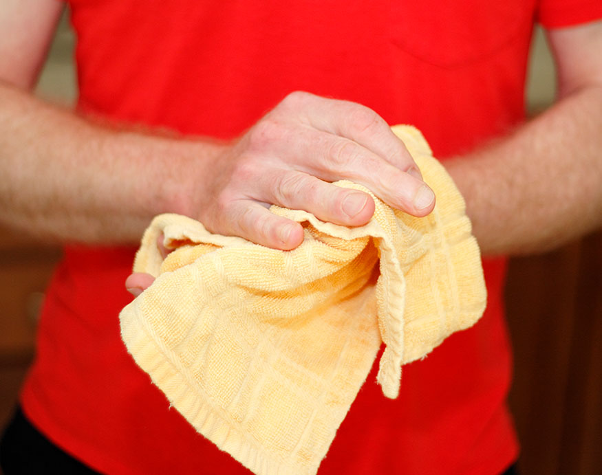 a person using a hand towel to dry hands